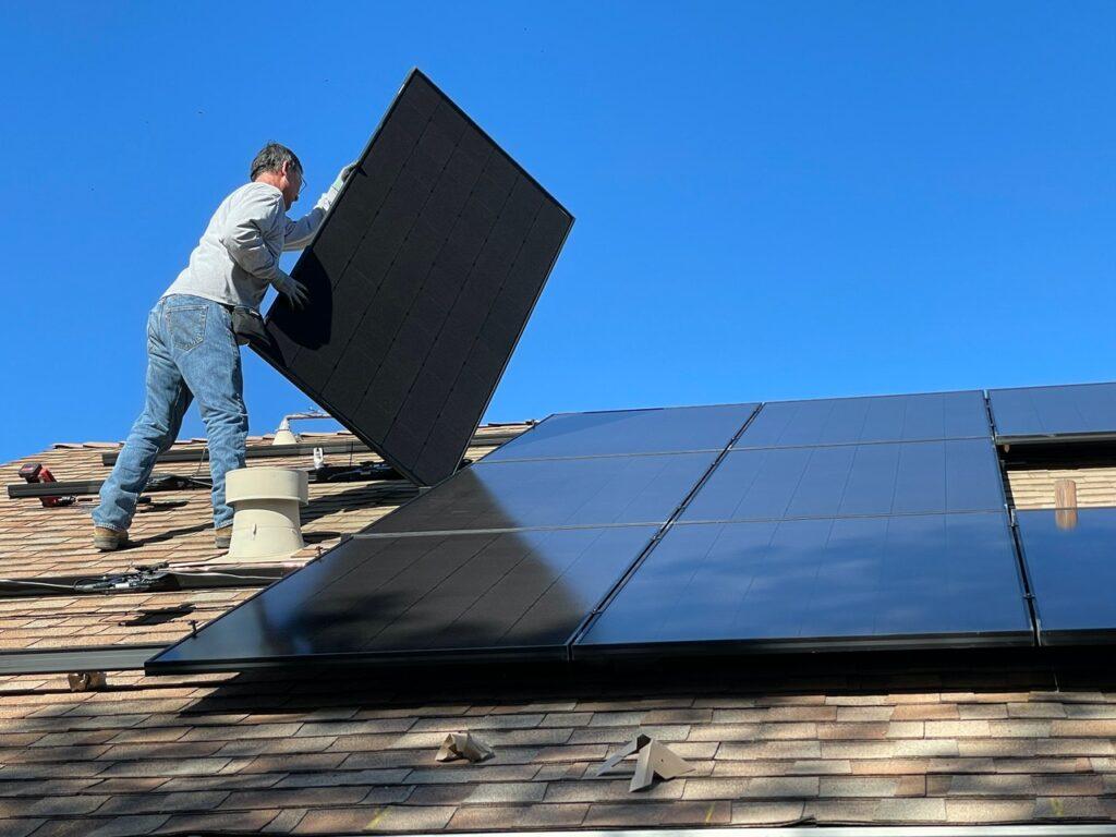 Man on roof installing solar panels.